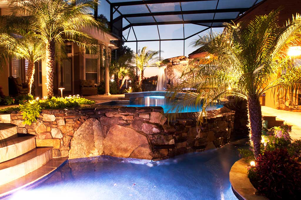 Lagoon pool with spa and infinity edge and a natural stone grotto, swim up barand outdoor kitchen and fireplace