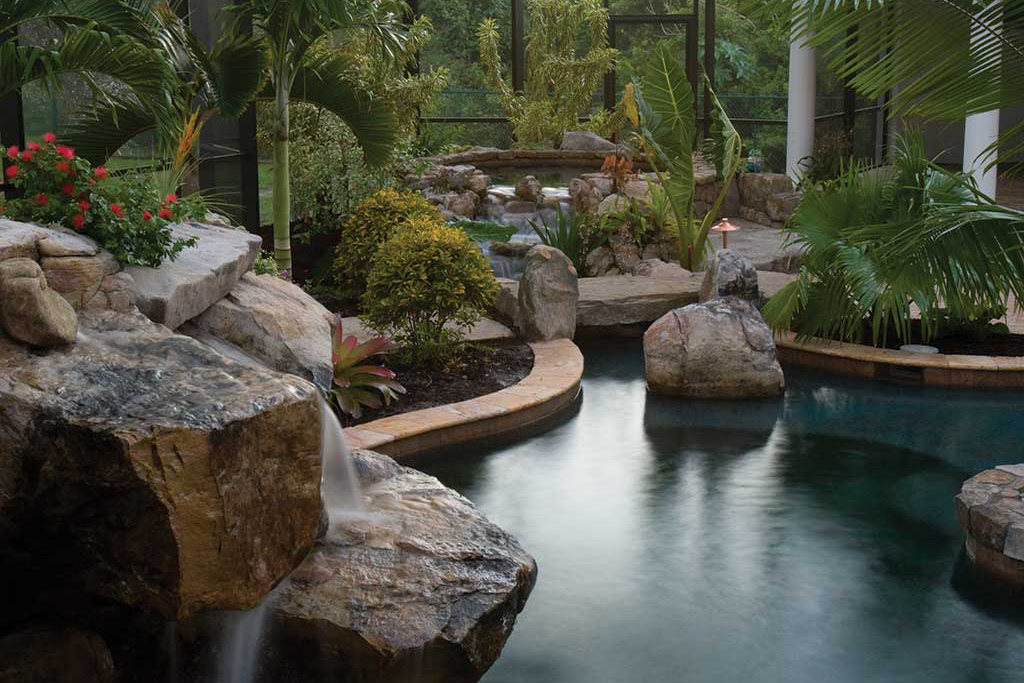 Lagoon pool and spa with spectacular grotto waterfalls and a stream connecting the spa to the pool, a natural stone bridge and tropical landscaping in Bradenton, Florida designed and built by Lucas Lagoons Inc.