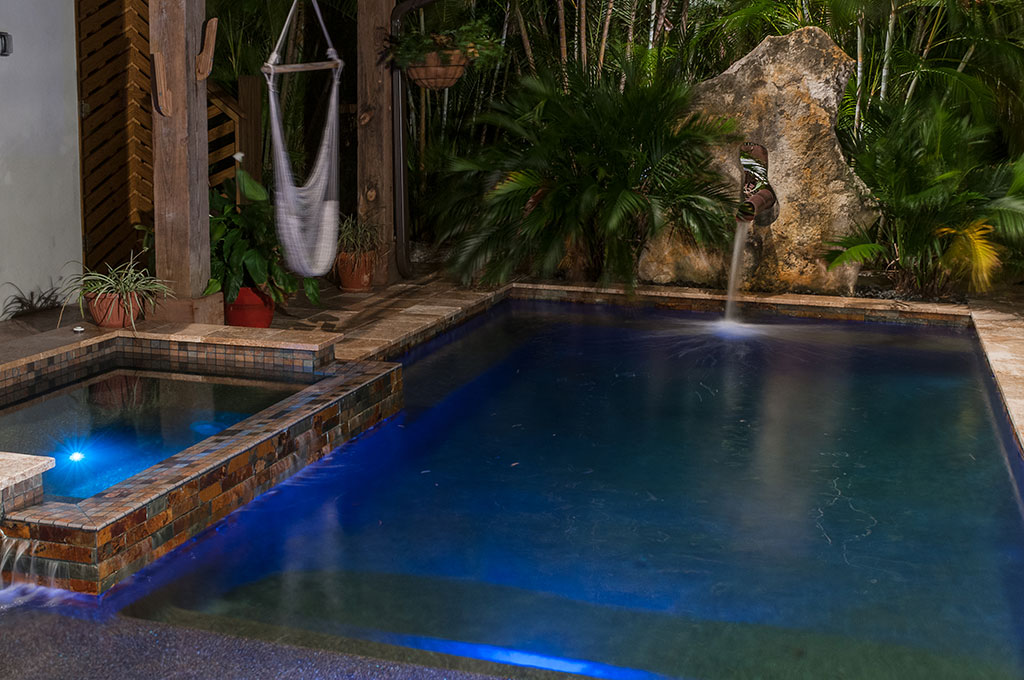 Modern Zen Pool and spa with copper scupper coming out of Limestone boulder designed and built by Lucas Lagoons Inc.