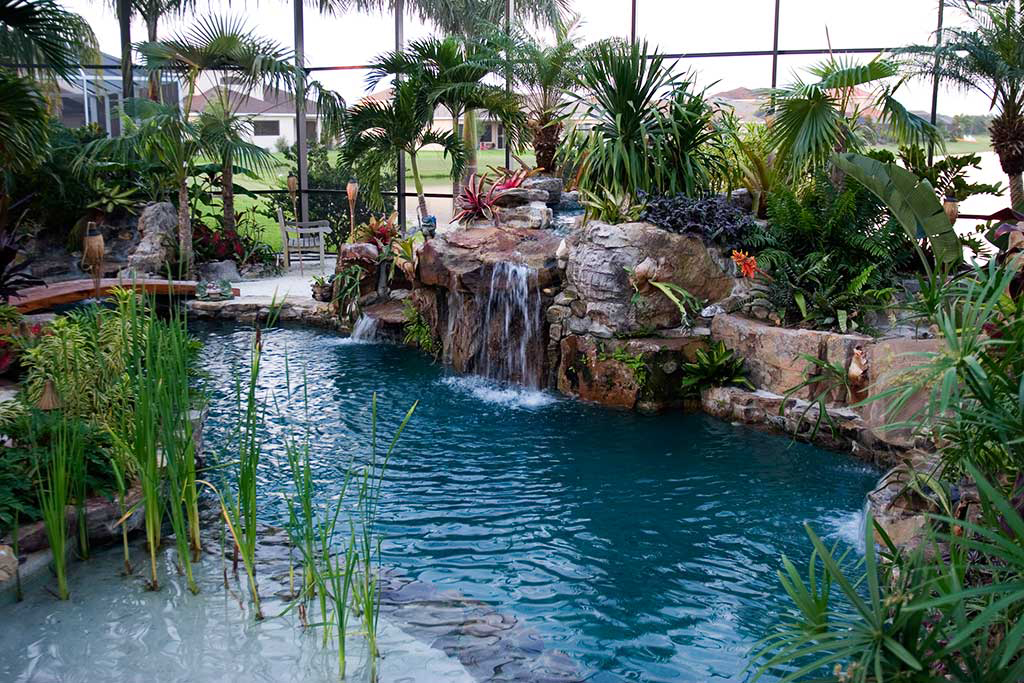 Lagoon pool with elevated spa and waterfall surrounded by Natural Tennessee Fieldstone with a beach areas and swim up bar designed and built by Lucas Lagoons Inc.