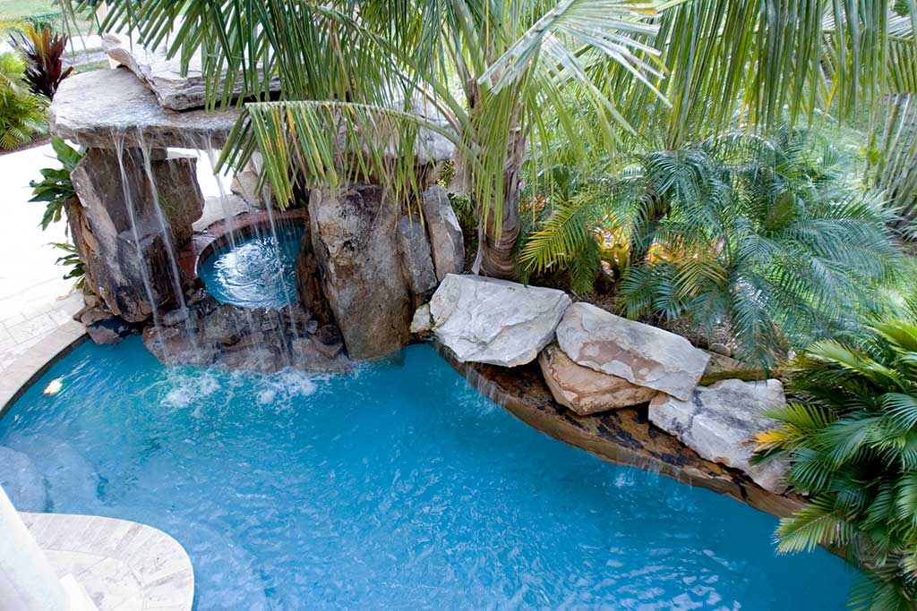Lagoon pool with spa underneath natural Tennessee Fieldstone grotto waterfall, Siesta Key, Florida designed and built by Lucas Lagoons Inc.