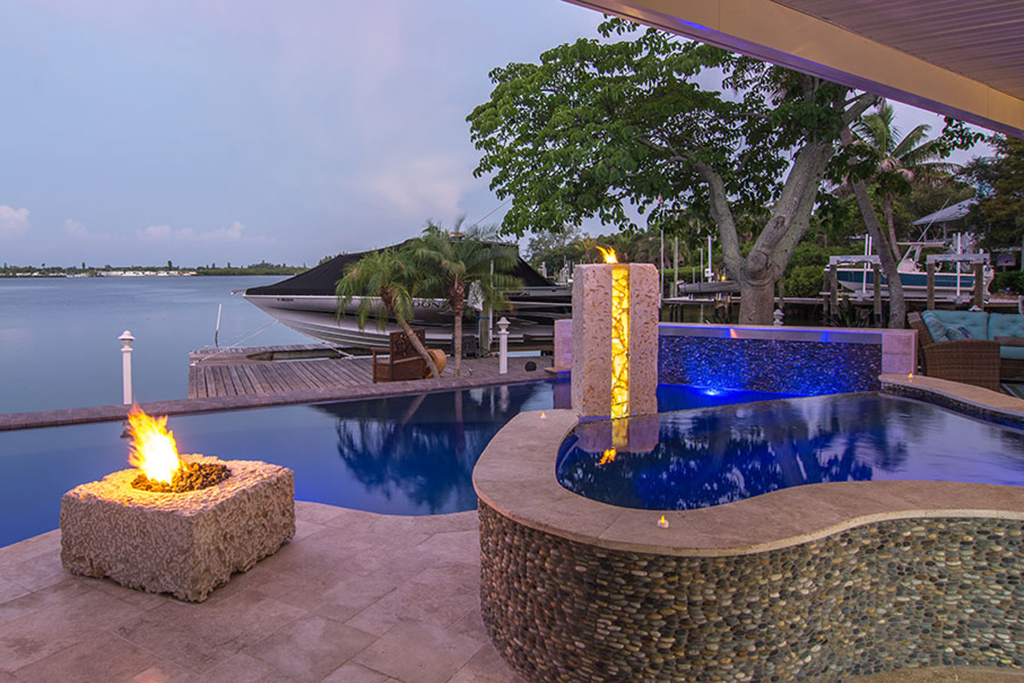 Lucas Lagoons designs a pool and spa both with infinity edges and a spectacular custom rock pillar fire feature and outdoor kitchen as seen on Insane Pools:off the deep end