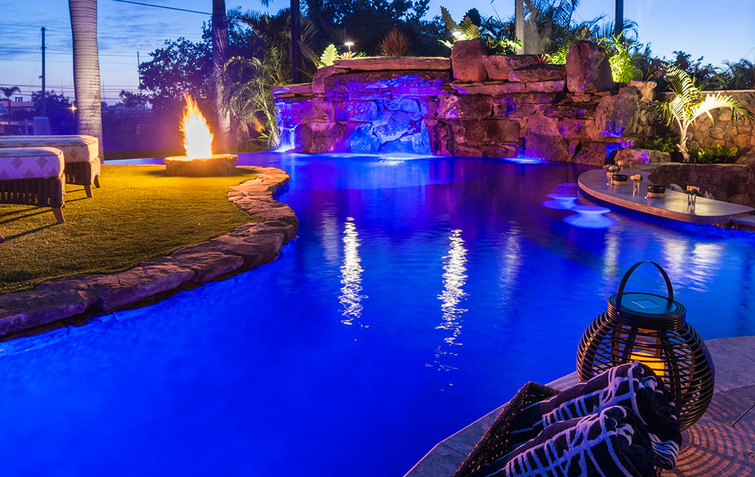 A Lazy River around an island with a fire feature in a Lagoon Pool with Infinity edge and Natural Stone Waterfalls designed and built by Lucas Lagoons Inc for the series Insane Pools on Animal Planet